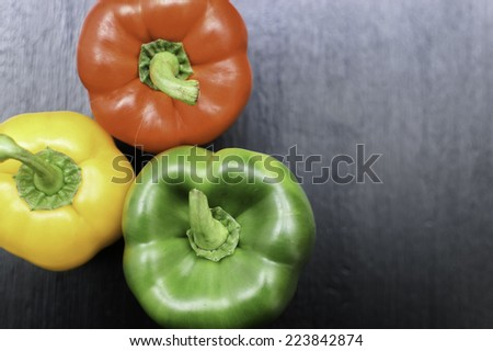 Three Bell Peppers on a dark wooden background. With Copy space.