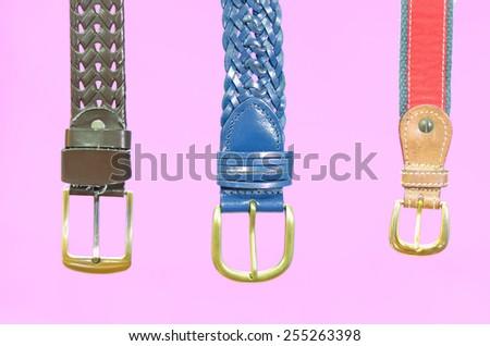 three belts on pink background - stock photo