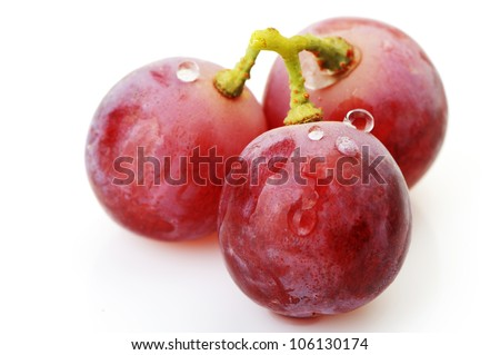 Three berries of red  grapes close up. It is isolated on a white background - stock photo