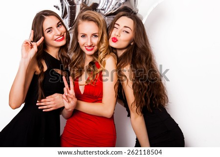 Three best friends celebrate  birthday indoor wearing elegant evening dress and have bright make up. Girls hugging and Showing signs with their hands. Looking at camera and smiling. Inside. - stock photo