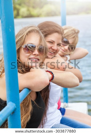 Three best friends having a good time outdoors by the water - stock photo