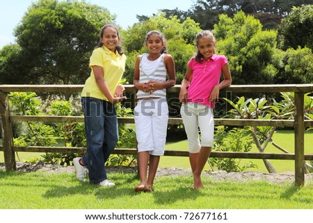 Three best friends leaning on a wooden fence