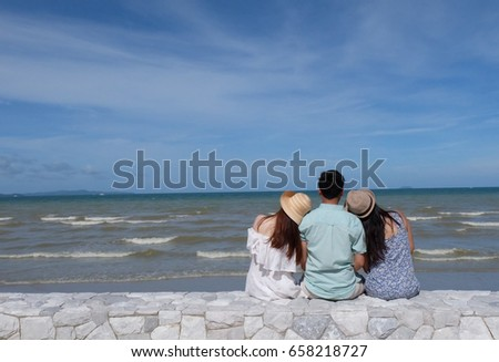 Three best friends look over the sky,discuss and think about the future so soon with a fresh air and wave sound surrounded on the beach