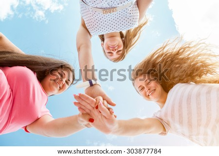 Three best friends looking down and holding hands outdoors - stock photo