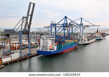 Three big cargo ships in Copenhagen seaport, Denmark; Cranes load cargo - stock photo