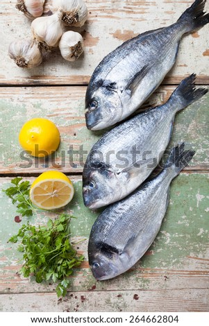 Three big fish (Sparus aurata) freshly caught on a wooden board - stock photo