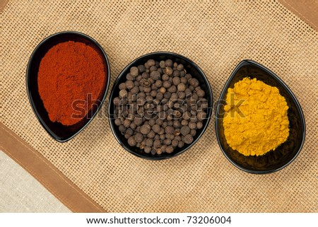 Three black bowls with different spices on brown natural background. Pepper corns, paprika and curry. - stock photo