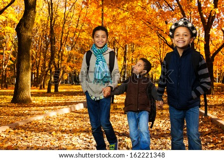 Three black boys, happy brothers 5-10 years old going together holding hands in the park wearing backpacks and autumn clothes in maple park - stock photo