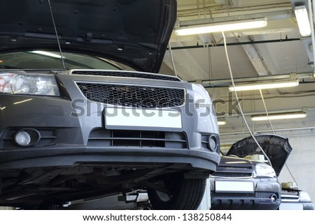 Three black cars on lifts with raised hoods in garage. Cars prepared to diagnosis and repair. - stock photo