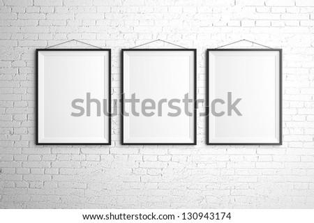 three black frames on brick wall - stock photo