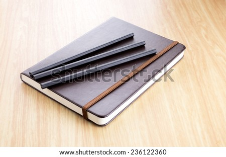 Three Black pencil on Brown Hard cover notebook with elastic strap on wooden table in perspective view - stock photo
