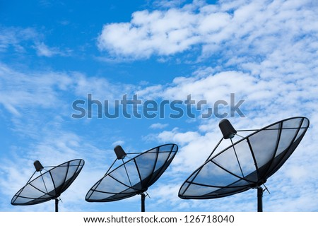 Three black satellite dish with cloudy blue sky background - stock photo