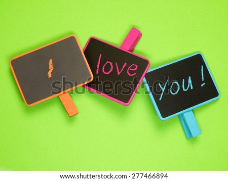 Three blackboards with I love you on a green background - stock photo