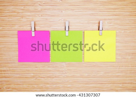 three blank color note papers. wooden background.