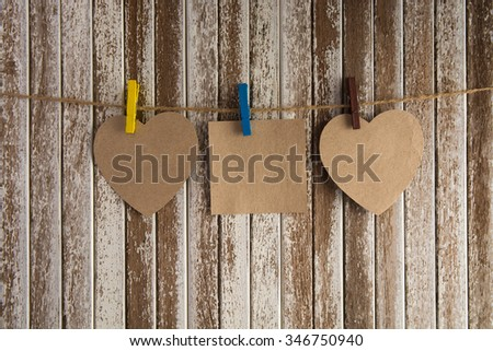 Three  blank paper washing line, with wood plank fence in the background vignette gives a retro or vintage feel. - stock photo