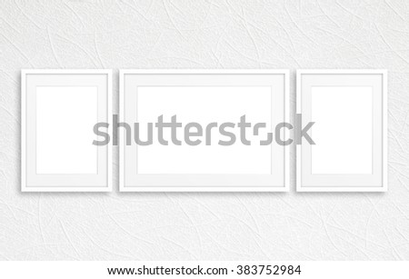 Three blank photo frames mockup on white textured wall