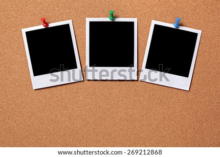 Three blank polaroid frame instant photo print, pushpin, cork background. - stock photo