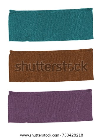 three blank textile labels of different colors