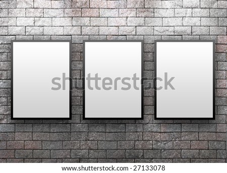 Three blank, white canvas frames are hanging on a brick wall. Light is shining down on them. - stock photo
