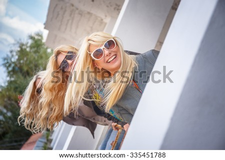 Three blondy women in sunglasses posing on camera. - stock photo