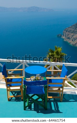 Three blue chairs and a small table on beautiful terrace in Santorini with Caldera view and Aegean sea. As always clear blue sky in hot Greece. Great atmosphere for vacation and holidays. - stock photo