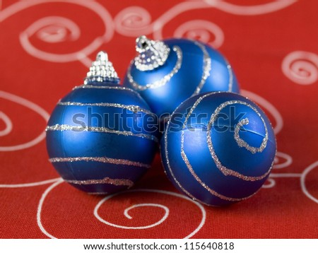 Three blue christmas balls on red background