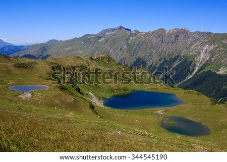 three blue mountain lakes in caucasus mountains surrounded with green grass of alpine meadows and forest on high rocky peaks behind in Abkhazia Georgia - stock photo