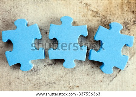 Three blue puzzle pieces on old canvas background
