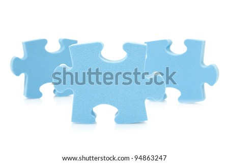 three blue  puzzle pieces over a white background - stock photo