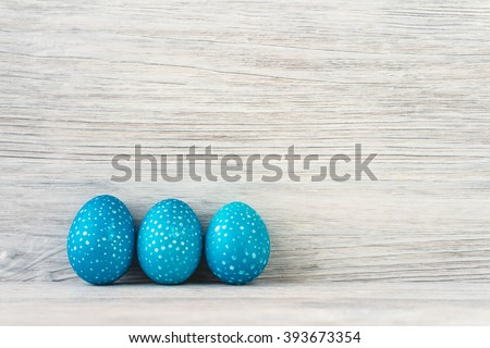 Three blue speckled Easter eggs on a white wooden background. Copy space. - stock photo