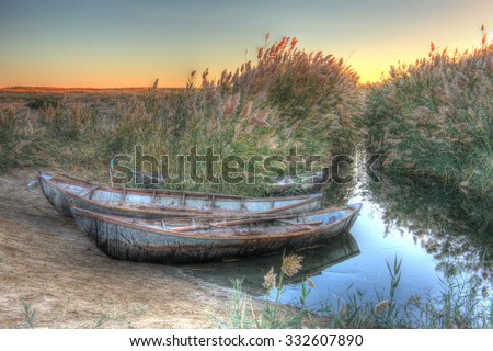 three boats in the reeds on the river Bank, dawn, hdr (high dynamic range imaging) - stock photo