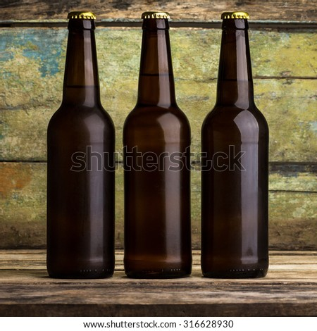 Three bottles of beer against wooden background - stock photo