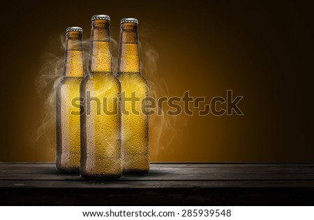 three bottles of beer with cold smoke over wooden table - stock photo