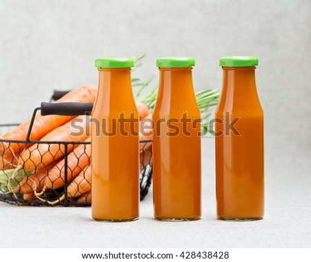 Three bottles of carrot juice and carrots in the basket. Selective focus. - stock photo