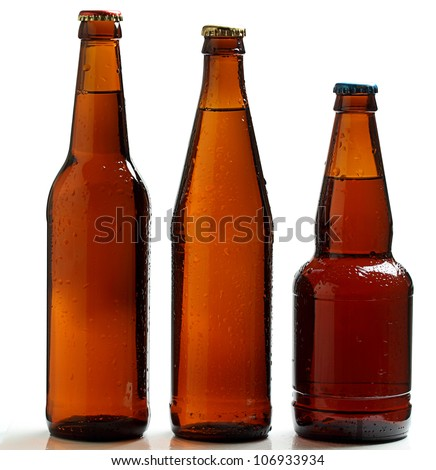 Three bottles of dark beer chilled on a white background. - stock photo