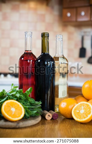 Three bottles of wine: white, rose and red, empty glasses and fruits on the kitchen table in a home kitchen interior - stock photo