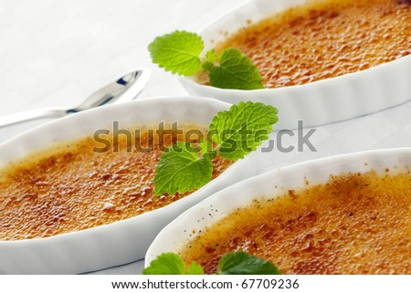 three bowls of creme brulee garnished with mint leaves, tilted view, closeup - stock photo