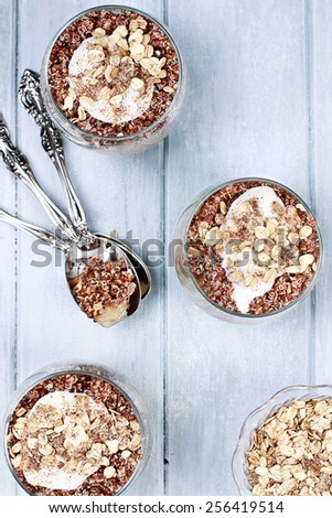 Three bowls of red quinoa with apples, yogurt and granola over a wooden blue background shot from above. Selective focus with shallow depth of field. - stock photo
