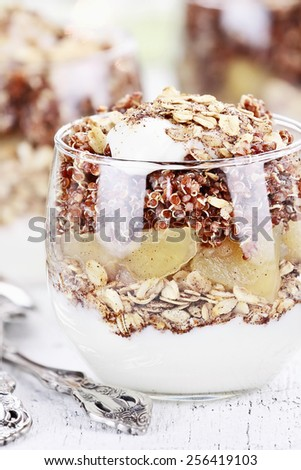 Three bowls of red quinoa with apples, yogurt and granola with shallow depth of field.