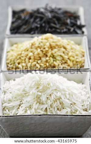Three bowls of white, brown and wild black uncooked rice - stock photo