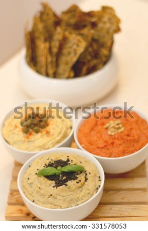 Three bowls with different dips: tuna dip, red pepper dip and hummus dip. Defocused crackers in the background.