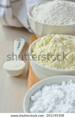 Three bowls with gluten free flour - rice flour, millet flour and potato starch and spoon with xanthan gum - stock photo
