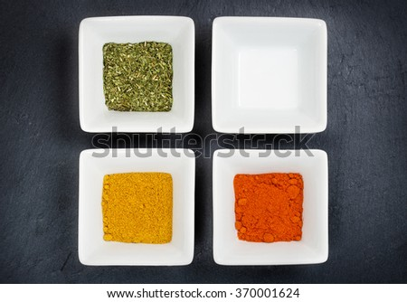 three bowls with spices and a blank one on grey background