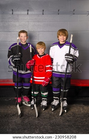 Three Boy Hockey Players are dressed in their gear in change room of arena - stock photo