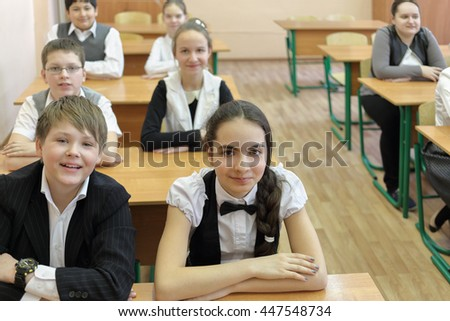 three boys and four girls in classroom sitting at desk in classroom, look at camera, focus on boy and girl in foreground