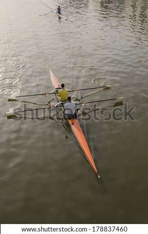 Three boys are rowing on two boats. - stock photo