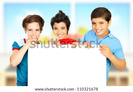 Three boys in classroom holding white clean board, happy children enjoying studying at school, smiling teenager having fun indoors, back to school, best friends concept, love to education - stock photo