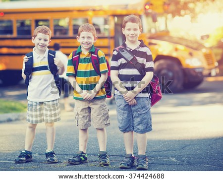 Three boys in front of a school bus - stock photo
