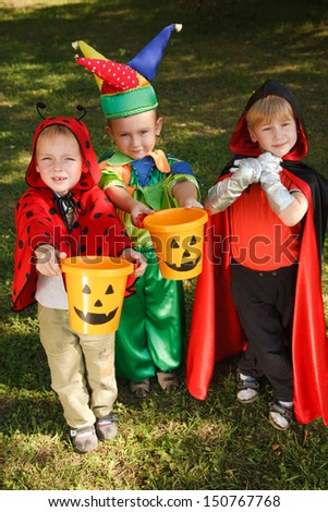 Three boys in halloween costumes are counting their candies - stock photo