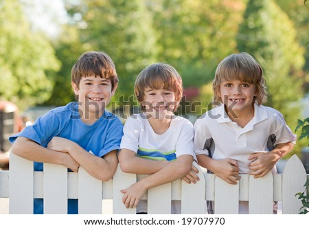 Three Boys on a White Picket Fence - stock photo